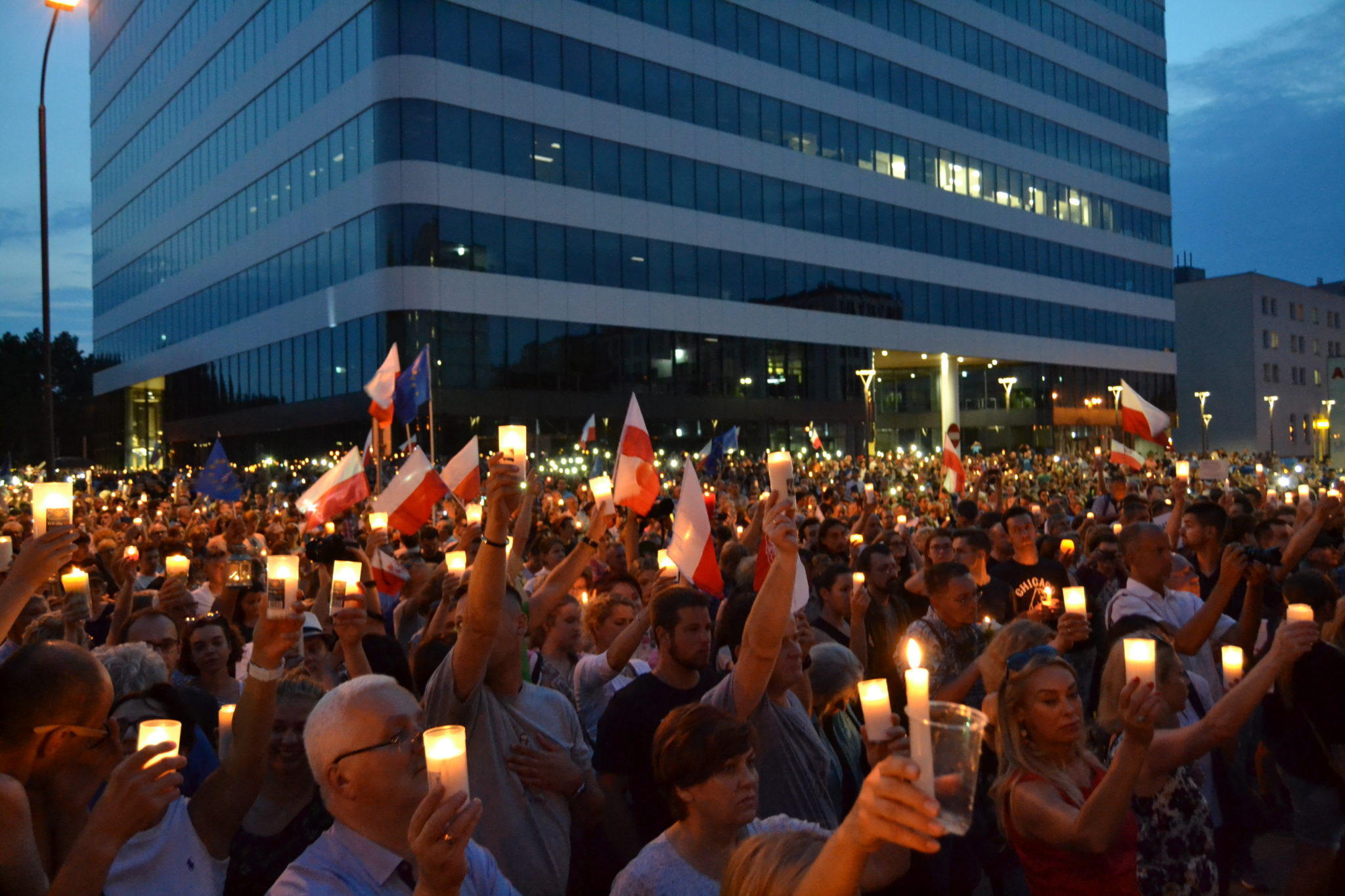 Demonstrators hold candles and flags in a silent moment of protest before the Polish court in Krakow Wednesday evening