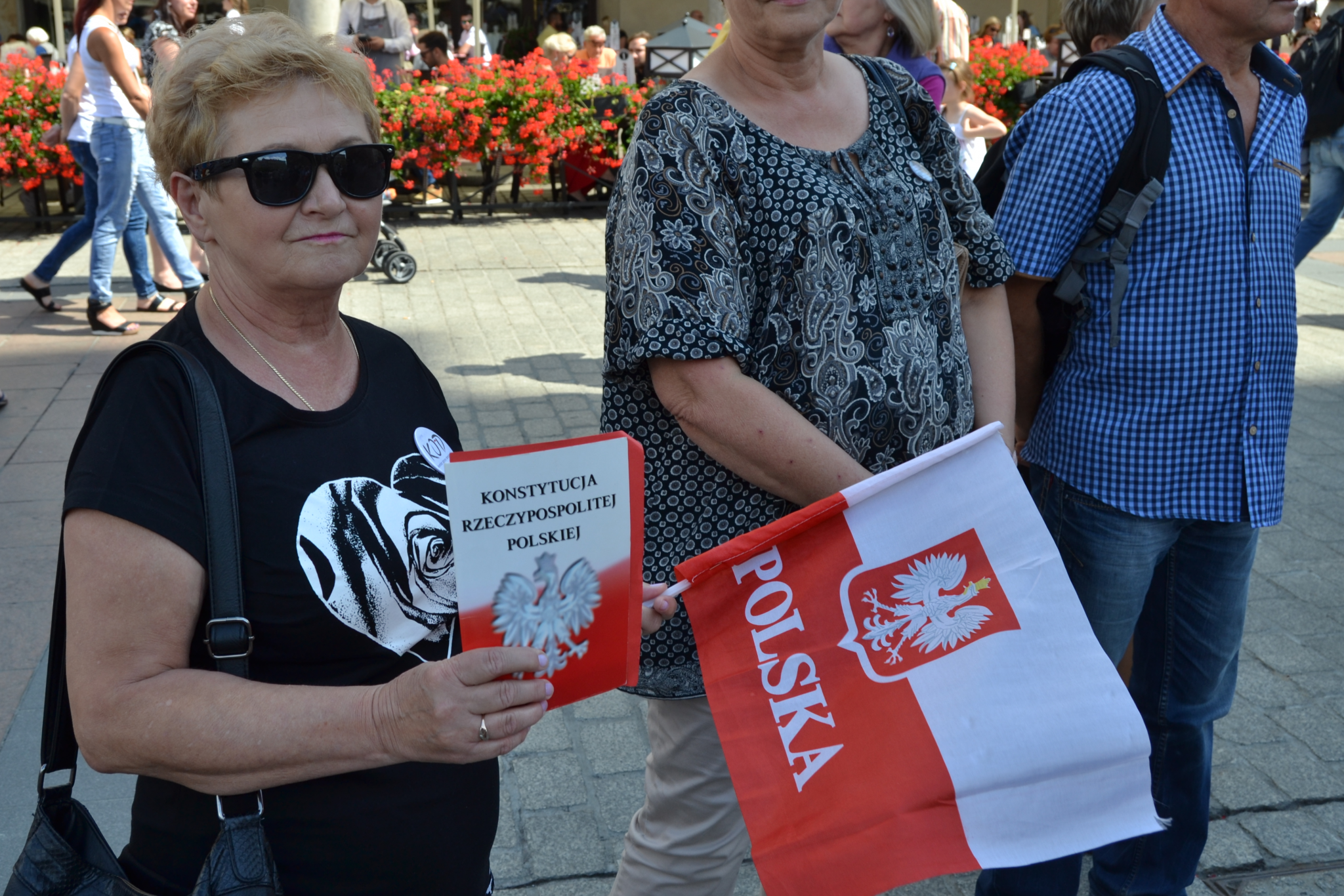 A Polish woman holds her flag and Constitution at the demonstration