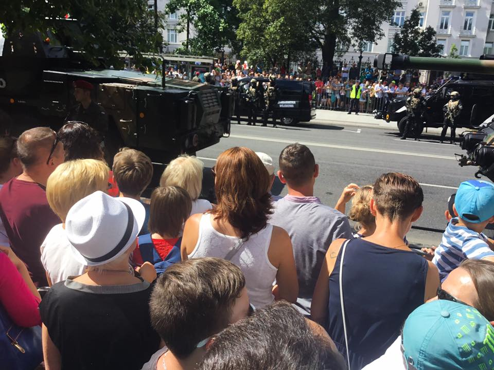 Onlookers watch as Polish military vehicles parade in celebration down the streets of Warsaw