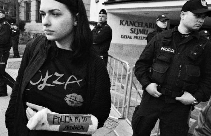 "An image from Amnesty International's report. At a peaceful counter-protest of a nationalist march in Warsaw, Anna reports she was detained in a police van for 1.5 hours without explanation and in the process suffered dislocation, sprain and tearing of joints and ligaments in her hand and wrist. Her cast says ""THE POLICE DID THIS TO ME"". (phot. JohnBob & Sophie Art)"